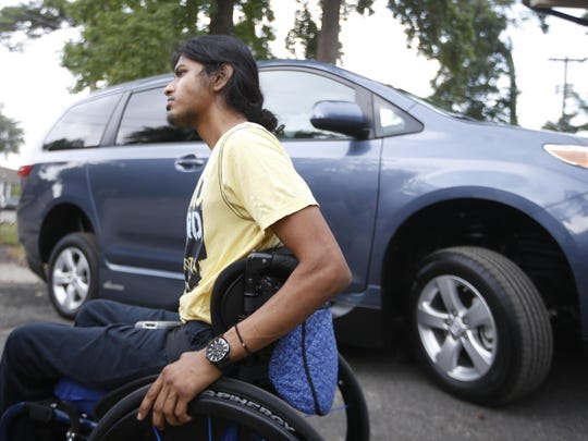 Ronny Ahmed sits outside of his newly modified van at Advanced Driving Systems on Monday.