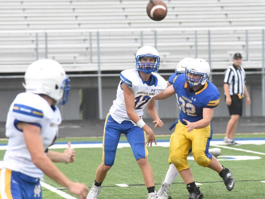 Mountain Home quarterback Eric Pederson (12) throws a pass during the Bombers' spring scrimmage on Thursday night.