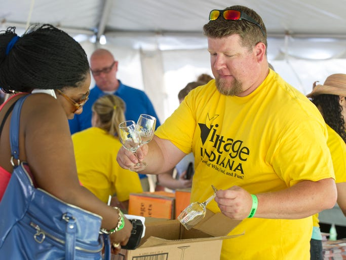 """Tom Pluimer, of Wolcott, hands out """"Vintage Indiana"""" wine glasses out to each ticket holder as they enter the festival. Billed as """"The Biggest Celebration of Indiana Wines,"""" the 15th Annual Vintage Indiana wine festival drew a huge crowd to Military Park in Indianapolis, Saturday, May 7, 2014."""