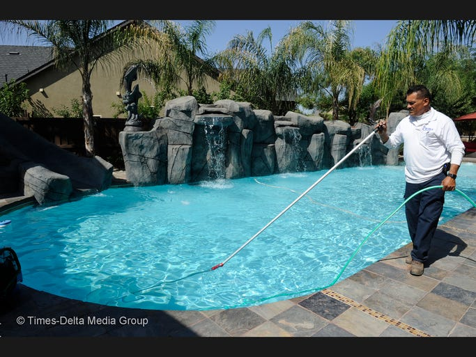 Ricardo Reyes vacuums a pool in the Del Lago neighborhood in Tulare. He owns Reyes Pool Service.