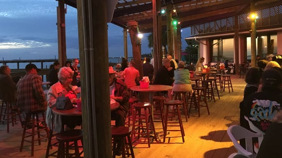 Friends and family guests enjoyed sitting on the waterfront deck Monday night during the soft opening of Squid Lips in Cocoa Beach. The restaurant officially opened at 4 p.m. Tuesday.