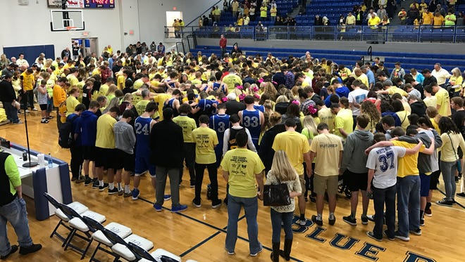 Players and spectators from White House and White House Heritage gather on the court following Tuesday's game to pray for White House High School student Mary Keith, who lost her battle with cancer on Tuesday.