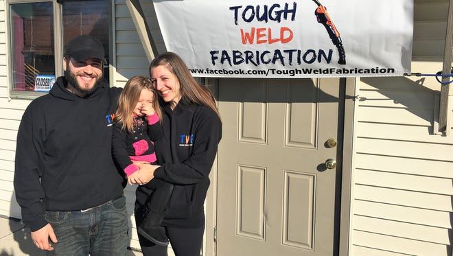 Tough Weld Fabrication owners Charlie, left, and Amanda Penrod, right, hold their daughter Quinn Penrod in front of their Marysville storefront.  Tough Weld Fabrication makes custom plasma-cut metal signs  and art for individuals and other businesses.