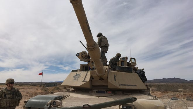 A tank crew with 1-67 Armor works in between rounds of gunnery out in the Fort Bliss training area.