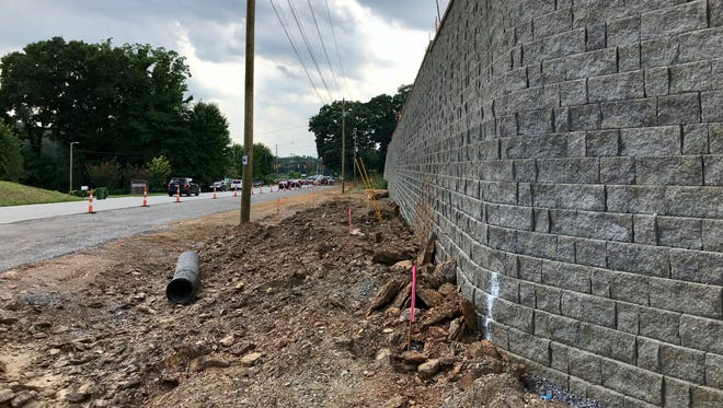 The developer of the Hawthorne on Mills Gap apartments says the appearance of this large retaining wall will be softened by a berm and landscaping running its entire length.