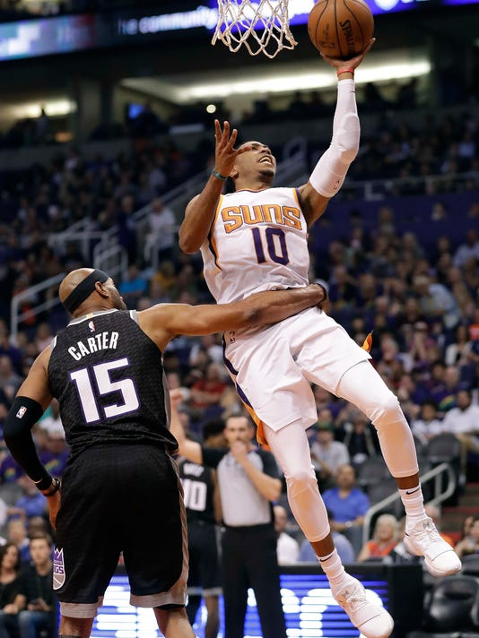 Phoenix Suns guard Shaquille Harrison (10) shoots asSacramento Kings guard Vince Carter (15) holds him back during the second half of an NBA basketball game Tuesday, April 3, 2018, in Phoenix. (AP Photo/Matt York)