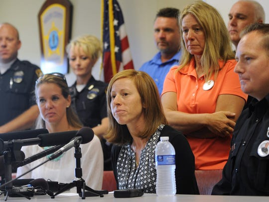 Surrounded by friends and family, Amy Ellis, center, talks about her husband Bardstown Police Officer Jason Ellis, during a press conference Tuesday, May 28, 2013 in Bardstown, Ky. Jason Ellis was ambushed and killed early Saturday morning, May 25, on his way home from work. (AP Photo/Patti Longmire)