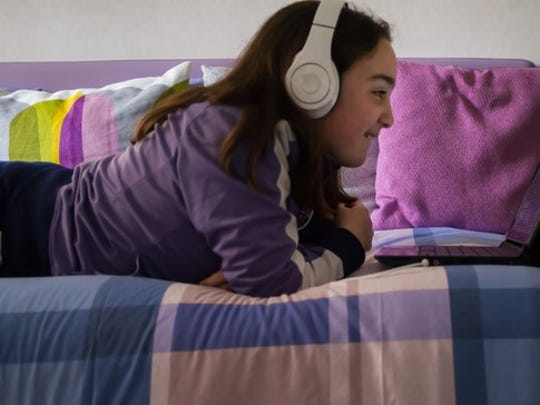 Girl laying on daybed smiling, wearing headphones watching laptop.