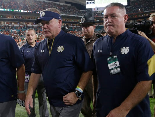 Notre Dame head coach Brian Kelly, left, walks to the locker room after the first half of an NCAA college football game against Miami, Saturday, Nov. 11, 2017, in Miami Gardens, Fla. Miami leads at halftime, 27-0. (AP Photo/Lynne Sladky)