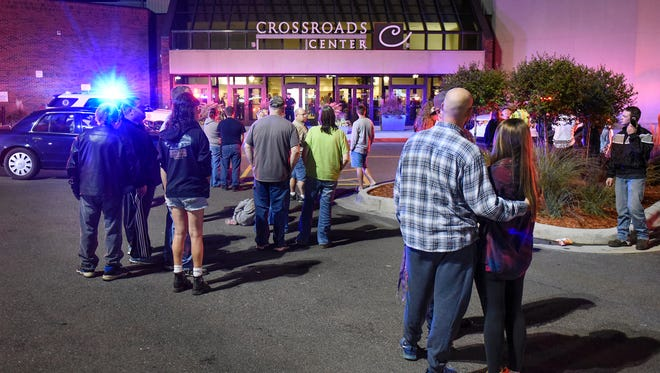 People stand near an entrance of Crossroads Center shopping mall on Sept.17, 2016,  in St. Cloud, Minn., after several people were stabbed.