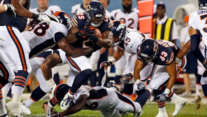 Chicago Bears running back Ka'Deem Carey (25) is tackled by Denver Broncos linebacker Vontarrius Dora (68) and defensive back John Tidwell (45) during the first half of an NFL preseason football game in Chicago, Thursday, Aug. 11, 2016.