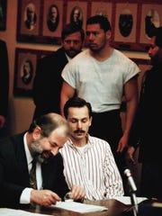 Jeff Gillooly second from left, ex husband to figure Skater Tonya Harding sits with his attorney Ron Hoevet, left, while Shane Minoaka Stant, right,  is led in to Multnomah country circuit court in Portland, Ore., Wednesday, Jan. 19, 1994 for their arraignment in connection with the assault on skater Nancy Kerrigan. Gillooly surrendered at the FBI office in Portland shortly after a warrant for his arrest was issued.(AP Photo/Jack Smith)