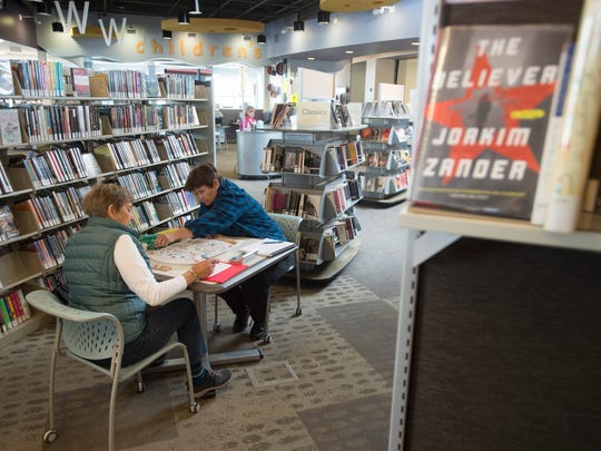 Joanie Woodrick and Barbara Peterson play a game of Scrabble between stacks of books at Council Tree Library on Tuesday, May 1, 2018.