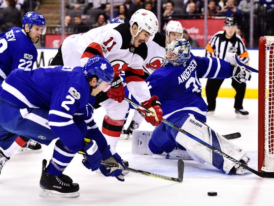 Toronto Maple Leafs goalie Frederik Andersen (31) stretches to make a save as New Jersey Devils center Brian Boyle (11) and Maple Leafs defenseman Ron Hainsey (2) look for a rebound during first period NHL hockey action, in Toronto on Thursday, Nov. 16, 2017.