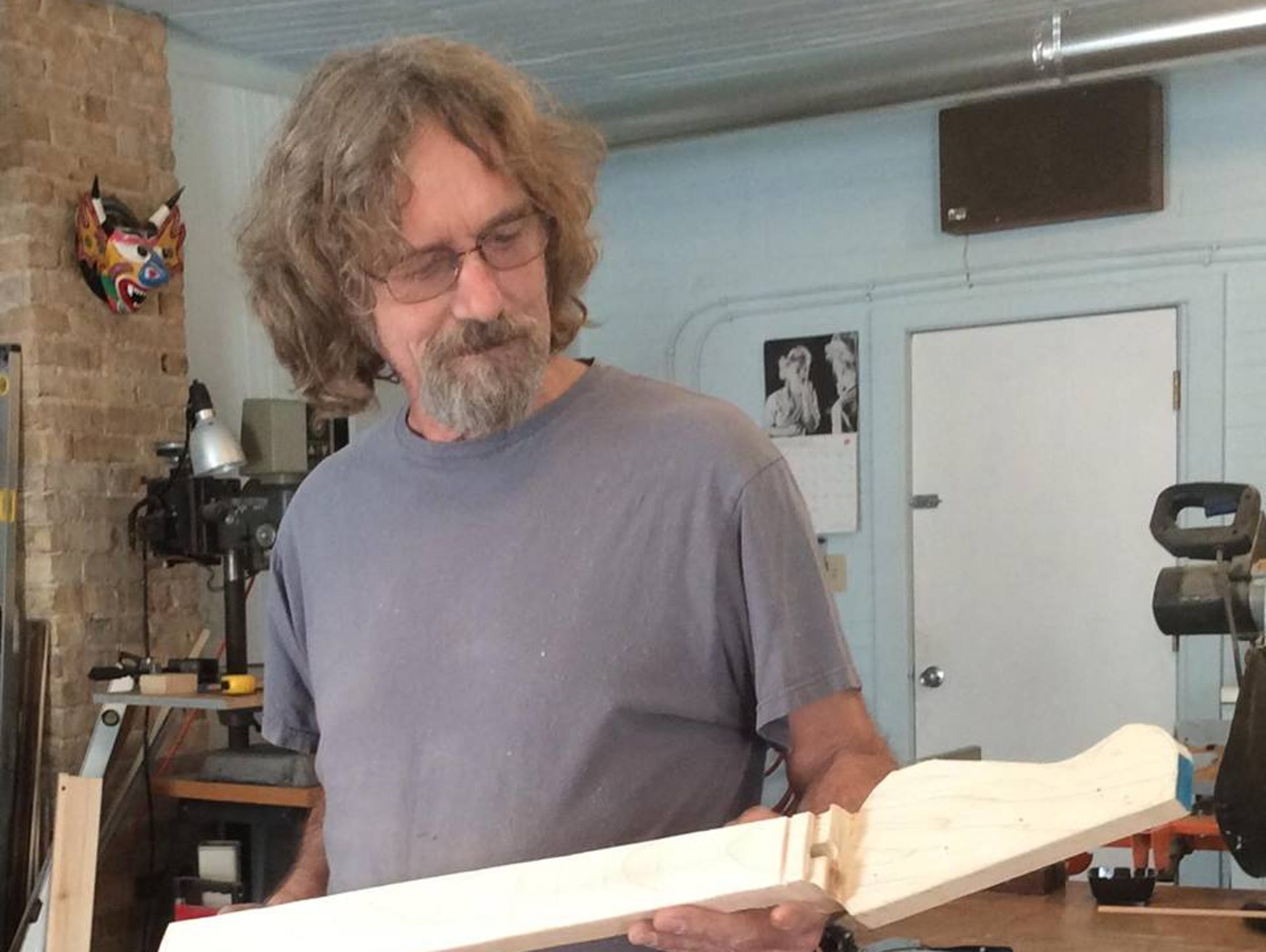 Tony Theisen of Fremont examines a guitar neck in his