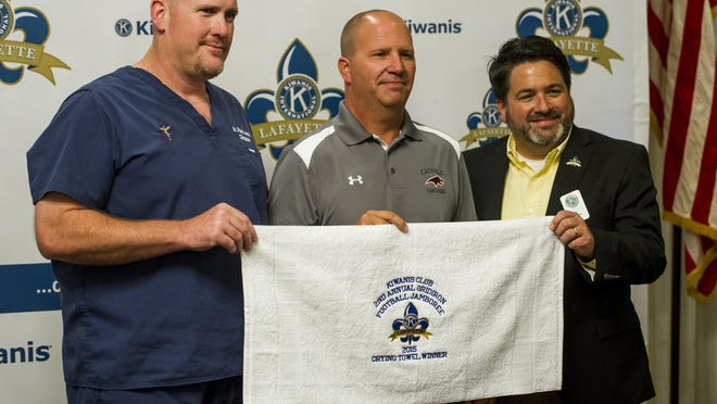 Brent Indest, head coach of Catholic High School of New Iberia, center, accepts the Crying Towel from Bob Lejeune, left, and Kiwanis Club president David Day during the Crying Towel luncheon hosted by the Kiwanis Club of Lafayette at the Petroleum Club in Lafayette Tuesday. The Kiwanis Club hosts the annual luncheon for coaches of high school teams participating in the club's football jamboree which will be held on August 27-28 at Cajun Field.