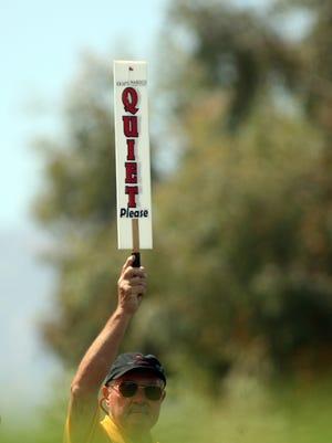 """A marhsal holds up a """"quiet"""" sign at a golf tournament."""
