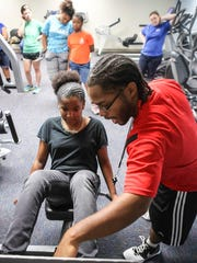Women's Wellness Camp participant Veronica Hayes, left, takes some advice from youth development specialist Jamayle West while learning how to use a leg press machine at the Cabbage Patch Settlement House.