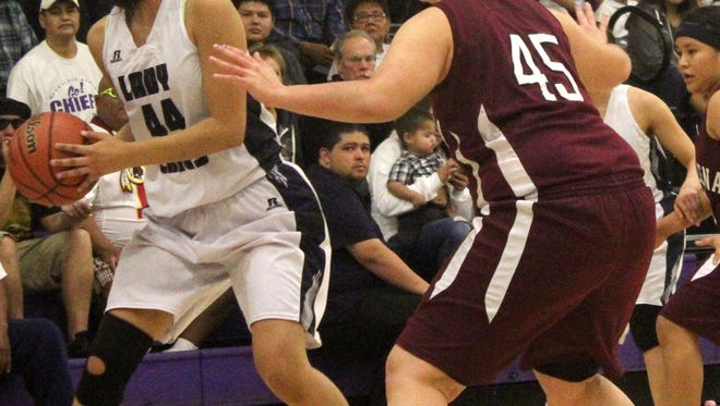 Mescalero's Lauryn Yuzos tries to find a open teammate while being guarded by Magdalena's Julie Zamora on Saturday afternoon at the Mescalero Apache School gymnasium.