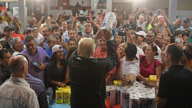 Trump arroja rollos de servilletas a la gente en Puerto Rico.