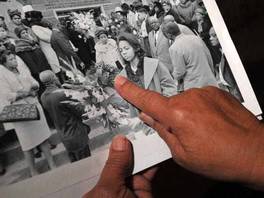 In this file photo taken April 1, 2010, Jeanette Smith points to herself carrying flowers in a photo taken at slain civil rights leader Vernon Dahmer's funeral in January 1966.