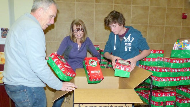 Mark, Ginger and Blake Houldsworth made it a family affair this year, preparing the Christmas Child shoe boxes and then packing them for delivery.