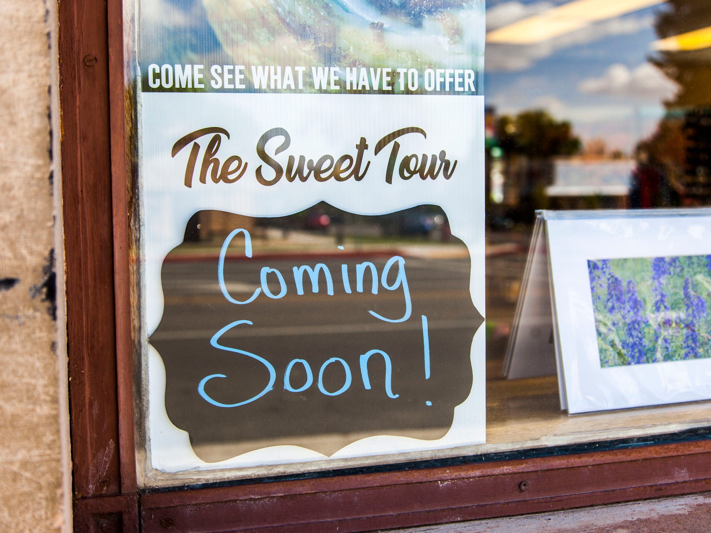 A sign for The Sweet Tour in sits in a window at the