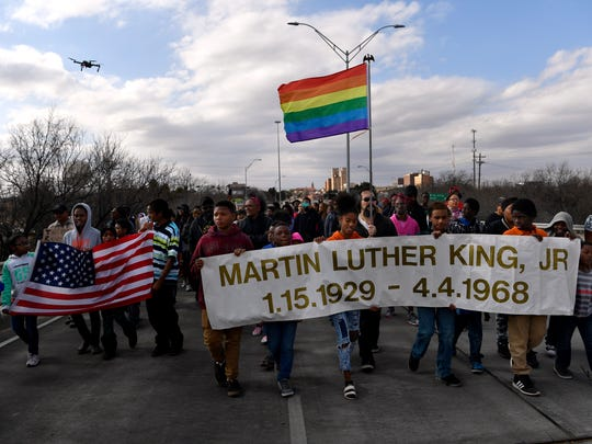 Marchers carry banners and flags during last year's Martin Luther King, Jr. parade across the bridge named after him.