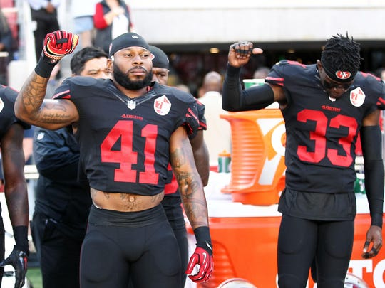 Oct 6, 2016; Santa Clara, CA, USA; 49ers strong safety Antoine Bethea (41) and cornerback Rashard Robinson (33) raise their fists during the national anthem before the game against the Arizona Cardinals at Levi's Stadium.
