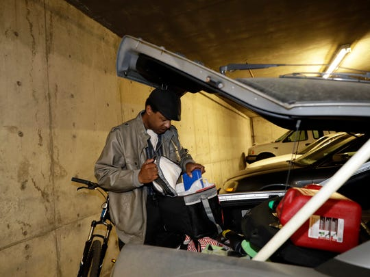In this photo taken Oct. 25, 2017, Albert Brown III, who works as a security officer, goes through the trunk of his car in San Carlos, Calif. Brown recently signed a lease for half of a $3,400 two-bedroom unit in Half Moon Bay, about 13 miles from his job. He can barely afford the rent on his $16-an-hour salary, even with overtime, but the car that doubled as his home needed a pricey repair and he found a landlord willing to overlook his lousy credit.