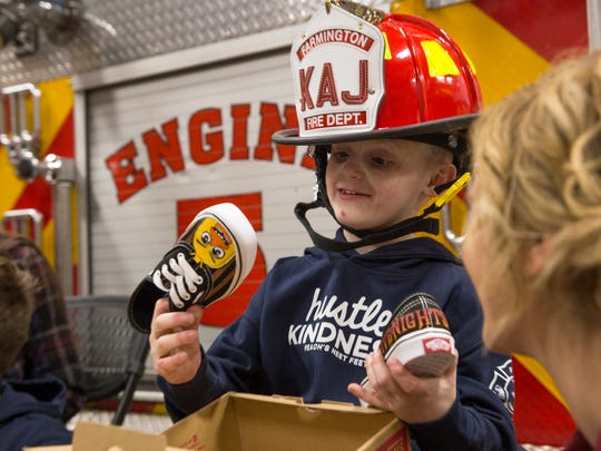 Kaj Shrode inspects a pair of shoes presented to him by Peach's Neat Feet founder Madison Steiner Friday at Farmington Fire Department Station 5.