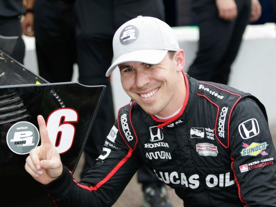 Robert Wickens, of Canada, poses for photos next to