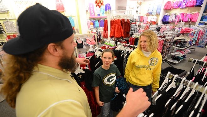 Green Bay Packers offensive lineman Josh Sitton talks with shoppers Sheryl Mielke, center, and Koral Meidam to see what they're buying during the Shop with Josh event at Kohls east December 2, 2014.
