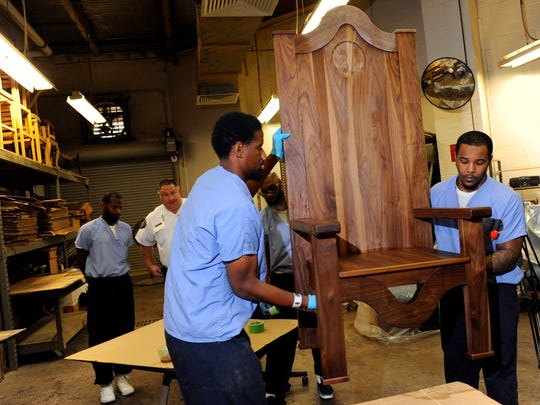 Rameen Perrin, left, and Evan Davis work on a chair designed for Pope Francis to use during his visit to a prison in Philadelphia. Perrin and Davis are inmates learning carpentry.