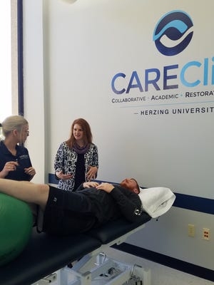 Halee Shepard, director of clinical education watches as students Ashley Borkenhagen and Thor Elsing practice. The CARE Clinic at Herzing University in Brookfield began seeing clients in July.