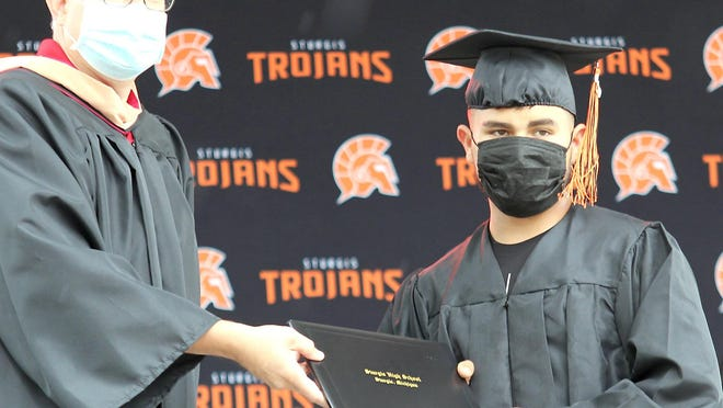 Jose Barrera Carrillo, one of 179 students from Sturgis High School class of 2020, receives his diploma Sunday from board of education president Scott Boland.