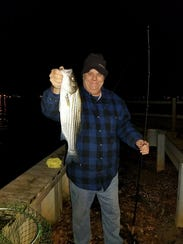 Chris Smith with a schoolie sized striped bass he caught