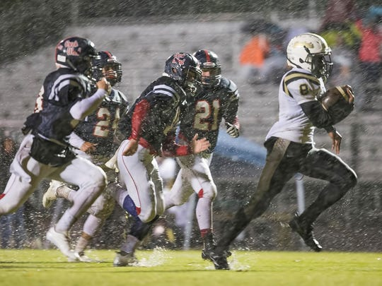 Springfield running back Keith Jones (8) is pursued by Creek Wood's Danny Stansberry (11), Kendell Lyles (21), Mitch Duke (24), and Sam Askins (13). Springfield defeated Creek Wood 42-0.