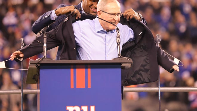 Michael Strahan puts the jacket on Tom Coughlin during the Ring of Honor ceremony.