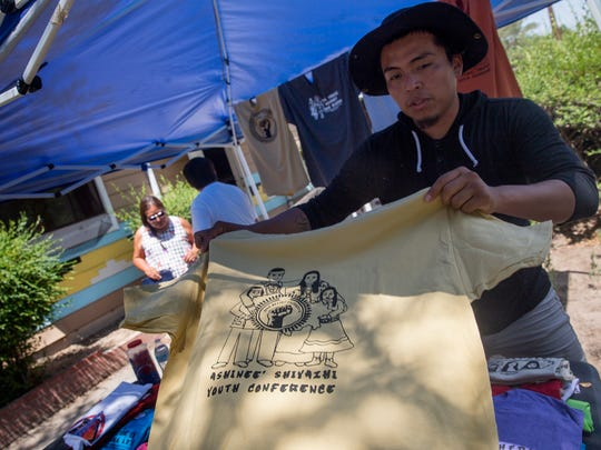 Event organizer Gjermundson Yazzie folds T-shirts Thursday at the Healing Circle Drop-In Center in Shiprock.