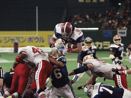 In this Jan. 12, 1992 file photo, East's Kevin Turner, of Alabama, dives over the top for a touchdown in the fourth quarter of the Japan Bowl, the American collegiate all-star football game, at the Tokyo Dome. A fullback at Alabama before playing eight years in the NFL for New England and Philadelphia, Kevin Turner was 46 when he died in 2016. He had been diagnosed with amyotrophic lateral sclerosis, known as ALS or Lou Gehrig's disease, but after studying his brain researchers declared that it was actually CTE.