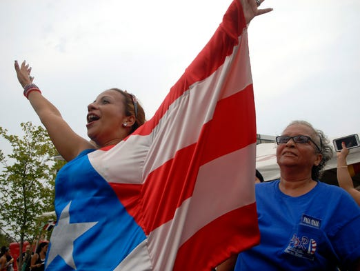 Puerto Rican Noemi Robinson (cq) celebrates at the 12th annual World Fest at the Belvedere.  Aug. 30, 2014