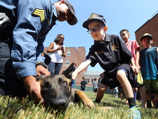 Ethan Geller, 7, pets K-9 Kiara as Sgt. Aaron Tomasini looks on. Ethan was honored as 'hero for a day' by the Morris County Sheriff's Office. Atlantic Health Systems/Goryeb Children's Center and the Sheriff's Office collaborated in showing Ethan around the courthouse and sheriff's office. June 24, 2016, Morristown, NJ