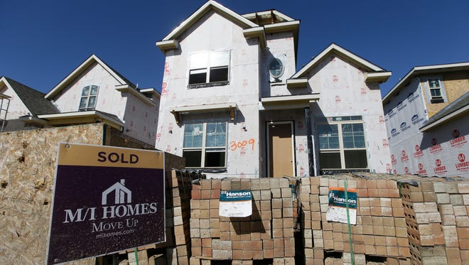 A sold sign sits in front of a house under construction in Plano, Texas.