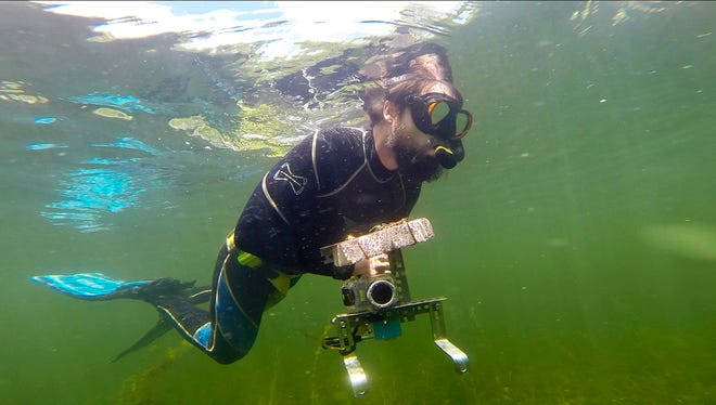 "Ben Maddox searches for fish to video record while snorkeling near Woods Island off of Hathaway Point in St. Albans on  July 17 . Maddox combines his video footage with his music for a video series called ""I See Fish People"" that he posts on YouTube."