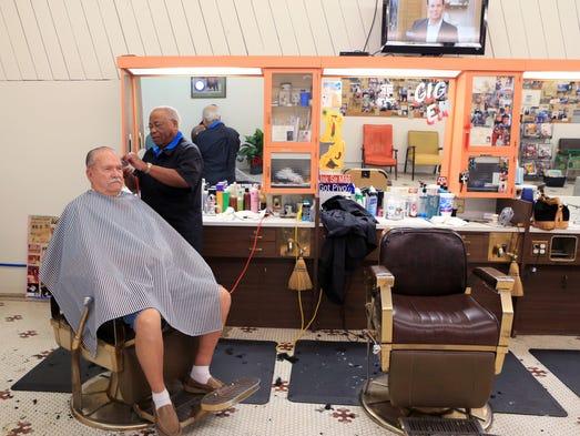 David Morris (right), owner of the King Barber Shop