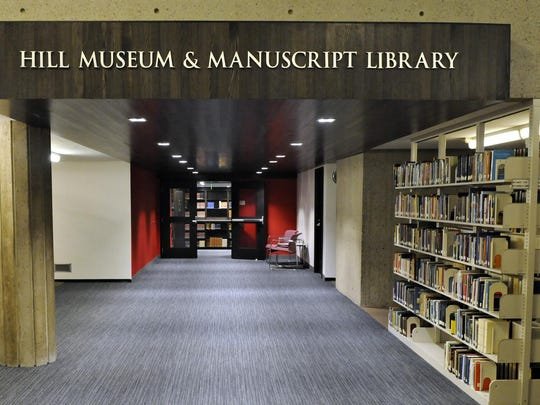 A Hill Museum & Manuscript Library sign marks the entrance to the institution on the lower level of the Alcuin Library at St. John's University.