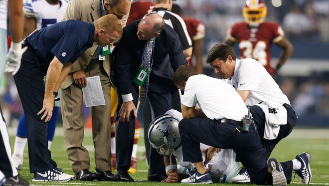 Dallas Cowboys quarterback Tony Romo lays on the field injured as trainers, doctors and head coach Jason Garrett check on him during a game against the Washington Redskins on Oct. 27, 2014, in Arlington, Texas.
