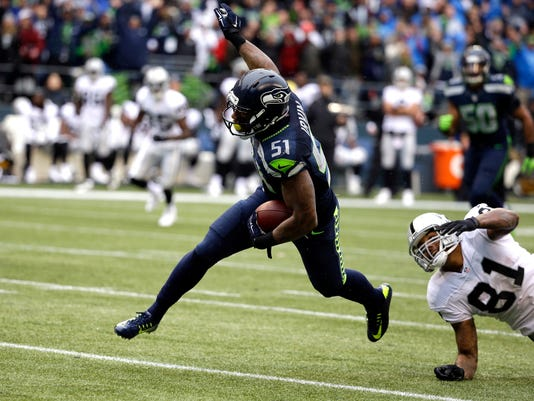 Seattle Seahawks outside linebacker Bruce Irvin (51) runs the ball as Oakland Raiders' Mychal Rivera (81) looks on after Irvin intercepted and ran for a touchdown in the first half of an NFL football game, Sunday, Nov. 2, 2014, in Seattle. (AP Photo/Elaine Thompson)