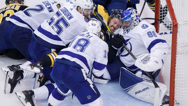 Boston Bruins left wing Joakim Nordstrom (20) is squeezed into the net against Tampa Bay Lightning goaltender Andrei Vasilevskiy (88) during the second period of an NHL hockey Stanley Cup playoff game Saturday in Toronto.